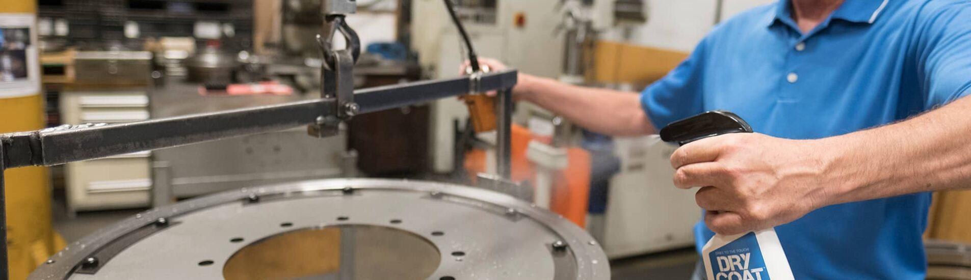 Worker spraying Dry Coat Rust Preventative on gear