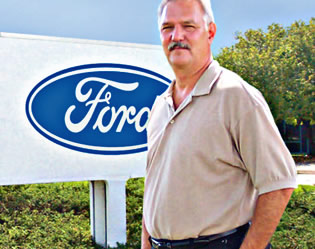 Man standing in front of Ford sign